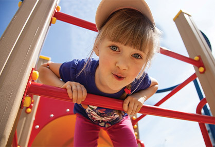 Girl playing on jungle gym at summer camp